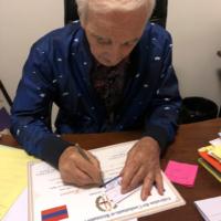 Charles Aznavour signe sa carte de membre de la FCRFA